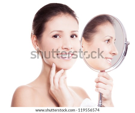portrait of a happy beautiful woman looking into the mirror, isolated against white background - stock photo