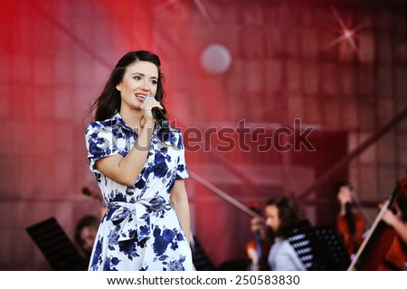 portrait of a happy beautiful woman on stage with microphone. - stock photo