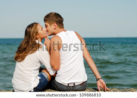 Portrait of a happy beautiful young couple man and woman kissing outdoors on the bright sunny day by blue sea over blue sky background - stock photo