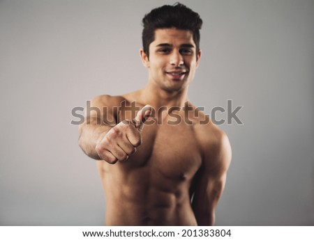 Portrait of a happy bodybuilder with muscular physique showing thumbs up sign. Shirtless young hispanic man on grey background. Focus on hand.