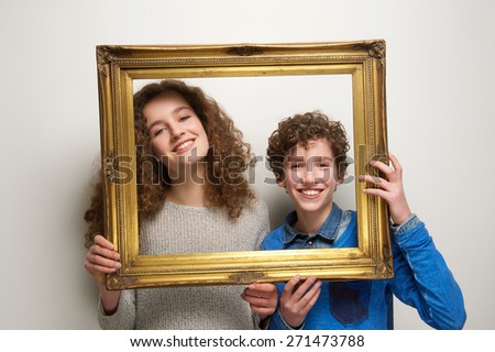 Portrait of a happy boy and girl holding picture frame - stock photo