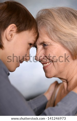 portrait of a happy boy and his grandmother over a gray background