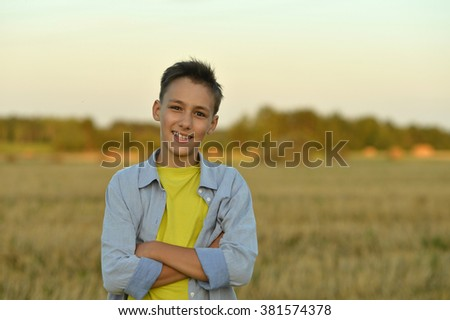 Portrait of a happy boy in field enjoying nature