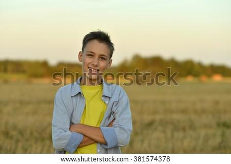 Portrait of a happy boy in field enjoying nature - stock photo