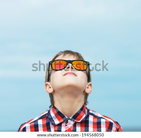 Portrait of a happy boy in sunglasses looking up