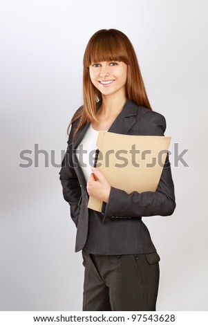 Portrait of a happy business woman holding a folder looking at camera Isolated on grey background - stock photo