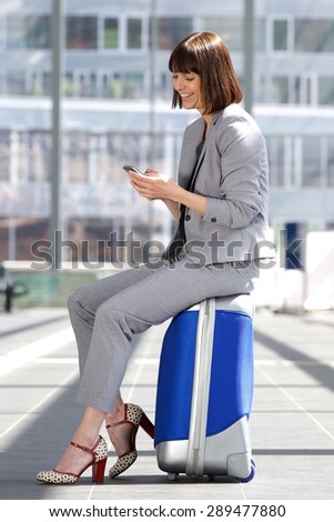 Portrait of a happy business woman sitting on suitcase at airport with mobile phone - stock photo