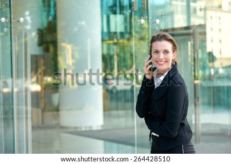 Portrait of a happy business woman walking and calling by cell phone outside