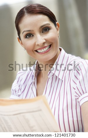 Portrait of a happy business woman with newspaper - stock photo