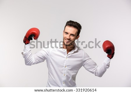 Portrait of a happy businessman in shirt wearing in red boxing gloves isolated on a white background - stock photo