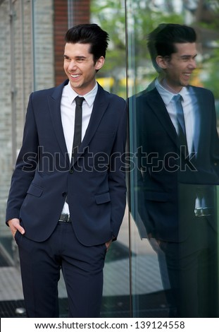 Portrait of a happy businessman leaning against glass building - stock photo