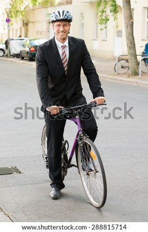 Portrait Of A Happy Businessman Riding On His Bicycle - stock photo