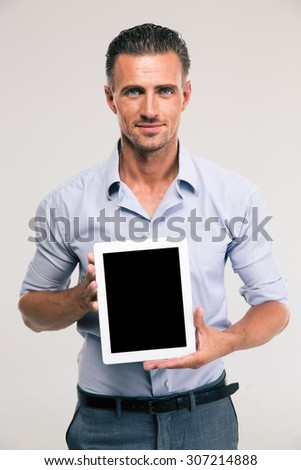 Portrait of a happy businessman showing blank tablet computer screen isolated on a white background - stock photo