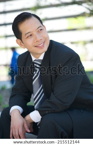 Portrait of a happy businessman sitting outdoors