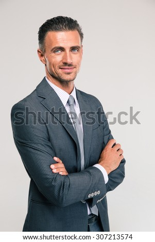 Portrait of a happy businessman standing with arms folded isolated on a white background - stock photo