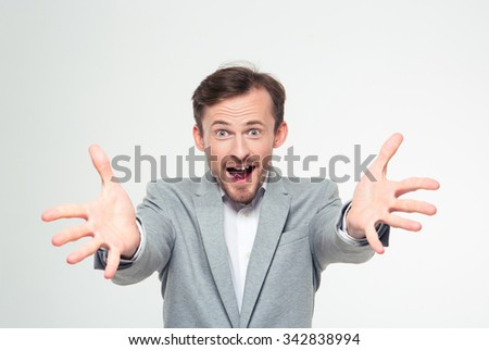 Portrait of a happy businessman stretching hands at camera isolated on a white background - stock photo