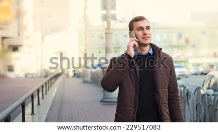 Portrait of a happy businessman walking outdoors with mobile phone