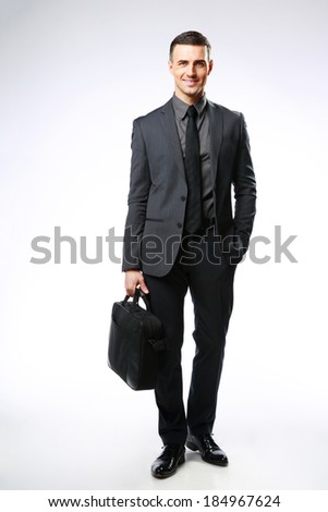 Portrait of a happy businessman with bag over gray background