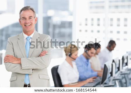 Portrait of a happy businessman with executives using computers in the office - stock photo