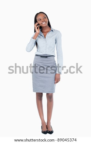 Portrait of a happy businesswoman making a phone call against a white background - stock photo