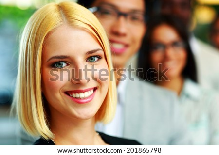 Portrait of a happy businesswoman standing in front of colleagues