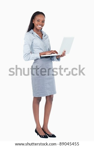 Portrait of a happy businesswoman using a laptop while standing up against a white background - stock photo