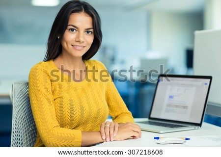 Portrait of a happy casual businesswoman in sweater sitting at her workplace in office - stock photo