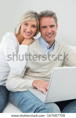 Portrait of a happy casual couple using laptop in the living room at home