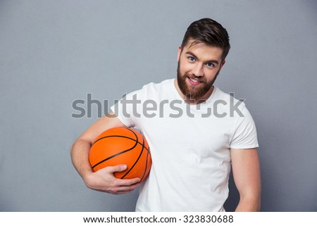 Portrait of a happy casual man holding basket ball over gray background
