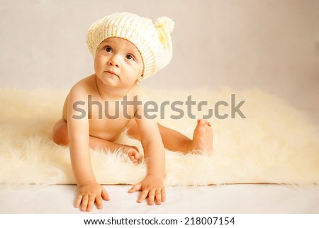 portrait of a happy caucasian adorable baby boy wearing hat - stock photo
