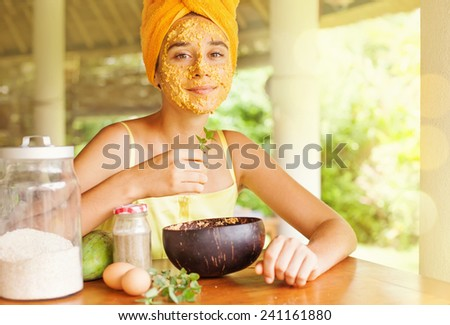 Portrait of a happy caucasian woman using natural secrets to do a skin care (ingredients are on a table: oats, flour, eggs, leaves) - stock photo