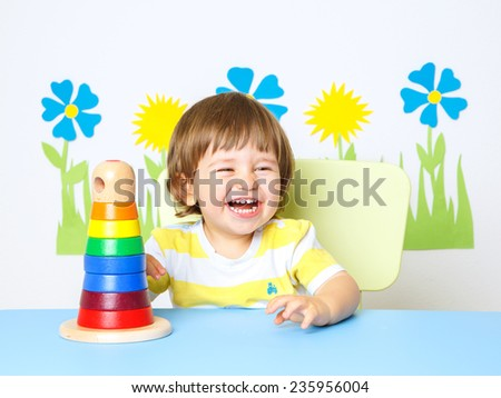 Portrait of a Happy cheerful baby at kindergarten or playgroup - stock photo
