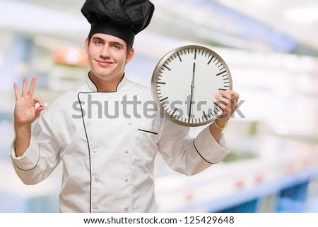 Portrait Of A Happy Chef Holding A Clock at a kitchen - stock photo