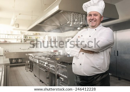 Portrait of a happy chef in the industrial kitchen with copy space