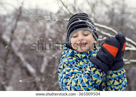 Portrait of a happy child boy in winter snow clapping hands in  big gloves.