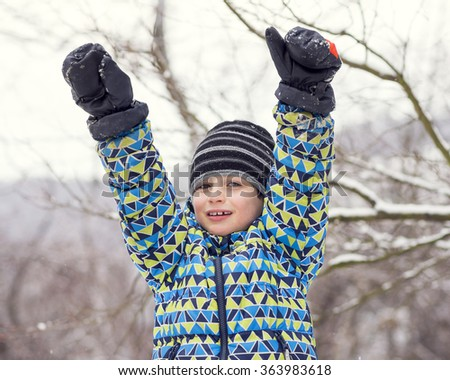 Portrait of a happy child boy in winter snow with hands up. - stock photo