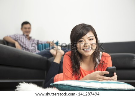 Portrait of a happy Chinese woman lying on lounge floor using a smart phone - stock photo