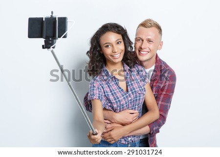 Portrait of a happy couple. Beautiful young girl standing smiling and making a photo using selfie stick while her happy smiling blond boyfriend hugging her from the back, isolated on grey background - stock photo