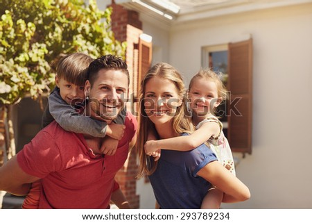 Portrait of a happy couple carrying their children on their backs. Parents giving their children piggyback rides in the backyard. - stock photo
