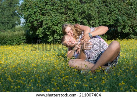 Portrait of a happy couple embracing and playing at the lawn.   - stock photo
