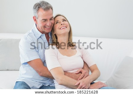 Portrait of a happy couple embracing in the living room at home