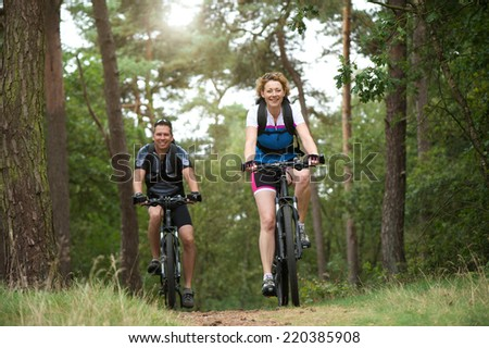 Portrait of a happy couple enjoying a bike ride outdoors - stock photo