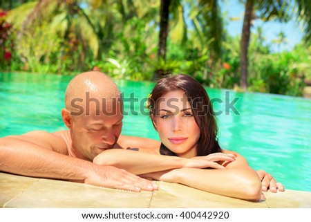 Portrait of a happy couple enjoying swimming pool, spending romantic vacation on tropical resort, summer holidays on paradise exotic beach - stock photo