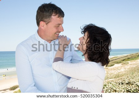 Portrait of a happy couple in love hugging on the beach at summer day with some vignette