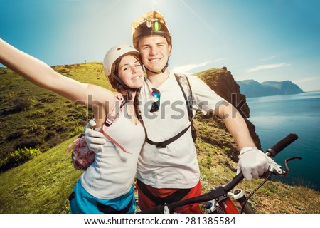 Portrait of a happy couple in the mountains with bicycles. Young man and woman traveling on mountain bikes outdoors. - stock photo