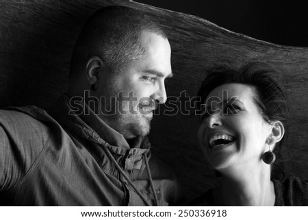 Portrait of a happy couple looking at each other, monochrome - stock photo