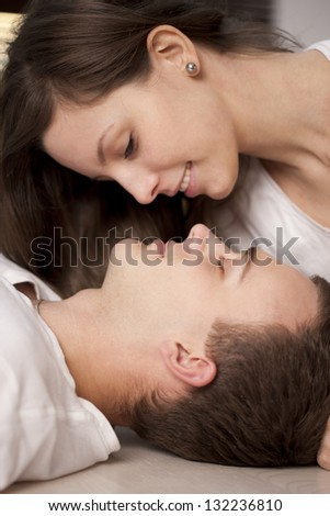Portrait of a happy couple lying on the floor - stock photo