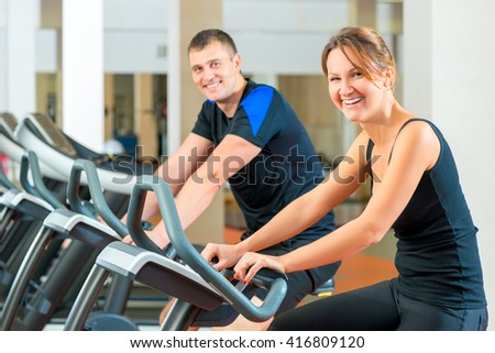 Portrait of a happy couple on a stationary bike in the gym - stock photo