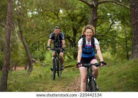 Portrait of a happy couple riding bicycles outdoors - stock photo