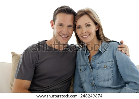 Portrait of a happy couple sitting on sofa at home - stock photo